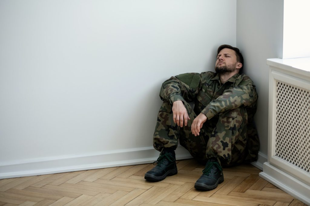 Depressed army man in uniform sitting in a corner of an empty ro